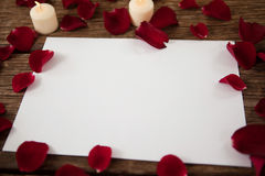 Wax candle and blank paper surrounded with rose petals Royalty Free Stock Photos