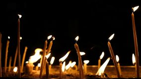 Wax candles burn in the dark in church against dark background, slow motion stock footage