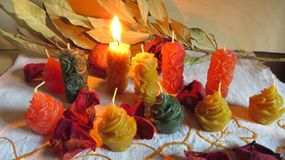 Wax candles in different colors and shapes and decorations in a simple composition. Wax candles of cake and rose shape in different colors in simple composition royalty free stock photography