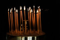 Wax candles in an orthodox church. Burning yellow easter  candles  in an orthodox church in greek Stock Image
