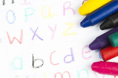 Wax crayons. On a sheet of paper with child's handwriting of alphabet letters stock photography