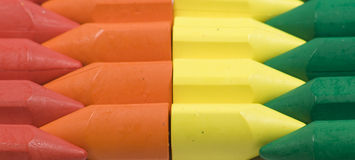 Wax crayons. Stacked in rows wax crayons, red,orange, yellow and green Royalty Free Stock Image