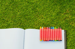 Wax crayons and sketchbook on fresh spring green grass Royalty Free Stock Photo