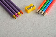 Wax crayons, a writing pencils and a sharpener. On a white background Royalty Free Stock Images