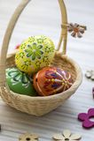 Wax painted Easter eggs in light brown wicker basket, wooden flower decorations. Wax painted Easter eggs in light brown wicker basket, wax ornaments, flower stock photos
