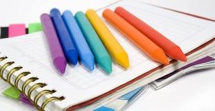 Wax pencils on notebook. Seven rainbow colors stock photos