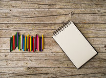 Wax pencils and notebook on wooden background Royalty Free Stock Photography