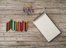 Wax pencils, paper clips and notebook on wooden background Stock Photography
