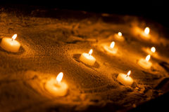 Wax sacred candles. On a sand Stock Image