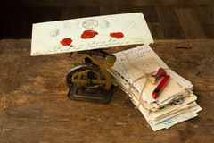 Wax seal and letter scale. Antique letter scale on an old wooden table with a bundle of letters Stock Photos