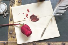 Wax sealed love letter with rose and quill on vintage background Royalty Free Stock Photo