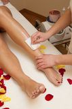 Waxing. Leg waxing in spa saloon Royalty Free Stock Images
