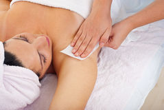 Waxing armpit. Close up of woman getting waxing armpit b y beautician in a beauty salon Royalty Free Stock Images