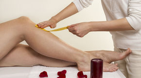 Waxing. Close up waxing in by a beautician in a spa center Royalty Free Stock Image
