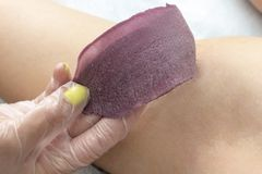 Waxing cosmetic depilation procedure removing wax from skin stock images
