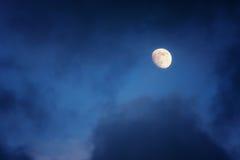 Waxing gibbous moon on cloudy sky Stock Photos