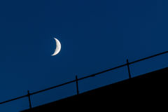 Waxing moon over construction scaffolding at night. Waxing moon over construction scaffolding silhouette at night royalty free stock photos