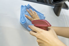 Waxing New Car. Woman waxing her new car using spray wax Royalty Free Stock Photography