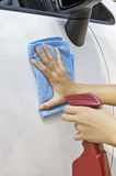 Waxing New Car. Woman waxing her new car using spray wax Stock Images