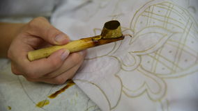 Waxing the patterns on the textile for batik stock video
