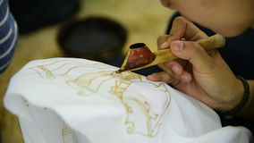 Waxing the patterns on the textile for batik stock footage
