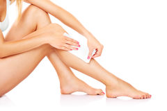 Waxing. A picture of a young woman waxing her legs over white background Stock Images