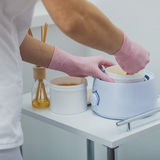 Waxing or sugaring epilation. Hands in pink glows making waxing or sugaring epilation Stock Photos