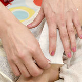 Waxing with wax strips. Beautician while making waxing with wax strips Royalty Free Stock Image