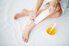 Waxing. Young Woman Depilating Her Leg With Wax Stripe.  stock photography