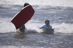 In the Way. A young girl rides a boogie board past her brother Royalty Free Stock Photo