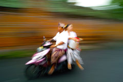 On the Way. Balinese couple on a motorcycle in the move Stock Image