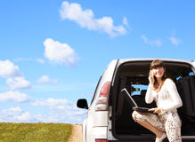 On the way. Young girl with laptop and phone in car Stock Images