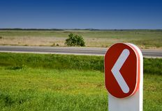 The way. Red sign near a road pointing left royalty free stock photo