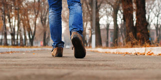 Way through  autumn park alley. Close up view on mans legs in blue jeans and boots walk through  autumn park alley Royalty Free Stock Photos