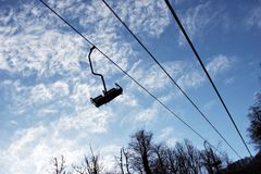 Way down. Empty chairlift on sky background Royalty Free Stock Photography