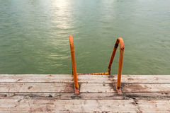 Way down, in to the water with orange bathing ladders. Royalty Free Stock Image