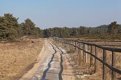 Way with fence. A way with a fence in a heath landscape in winter stock photography