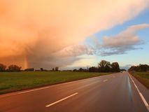 Way, field,rainbow and cloudy sky, Lithuania royalty free stock photography