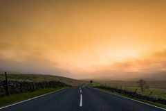 Way forward. Sunrise behind a road in Yorkshire Dales, England Stock Image