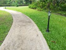 Concrete walkway on green grass field. The way in garden. Concrete walkway on green grass field Royalty Free Stock Image