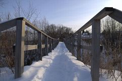Way Home. Bridge across the river in winter village Royalty Free Stock Photo