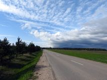 Road, trees, field and beautiful cloudy sky, Lithuania royalty free stock image