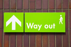 Way out sign with green background and white writing. Green way out sign with white writing, and upwards facing arrow and pedestrian image. Sign against brown stock image