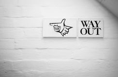 Way Out Sign on white brick wall. Stock Photos