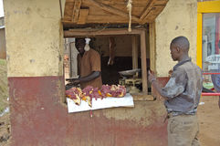 The way people life in Uganda. Butcher selling meat to his neigh Royalty Free Stock Photos