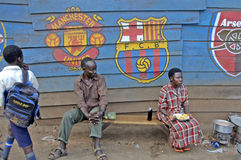 The way people life in Uganda. Man and woman having a break while boy is passing by. stock photo