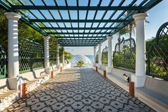Way with pergola to Dome in Kalithea Rhodes, Greece - Text tra. Nslation: `Reps sneaking through the rocks royalty free stock photo