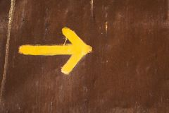 Way of Saint James yellow arrow on a rusty brown metal Sheet background Stock Photo