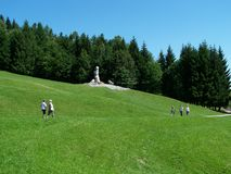 Way in spas across the meadow. Below the statues, green meadow and forest trees around, people walking through the meadow Stock Photos
