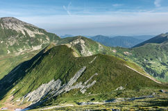 Way through summer mountains under blue sky with clouds Royalty Free Stock Photos